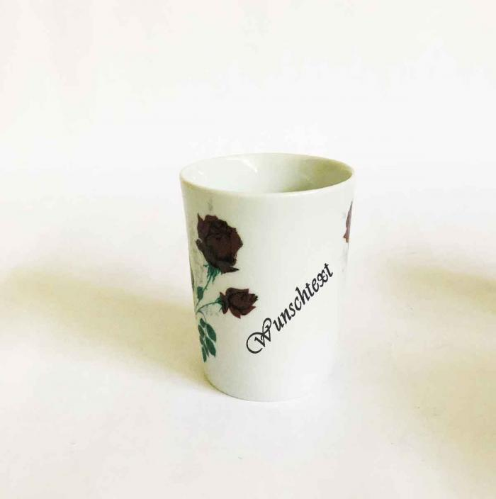 cup with two branches of red roses